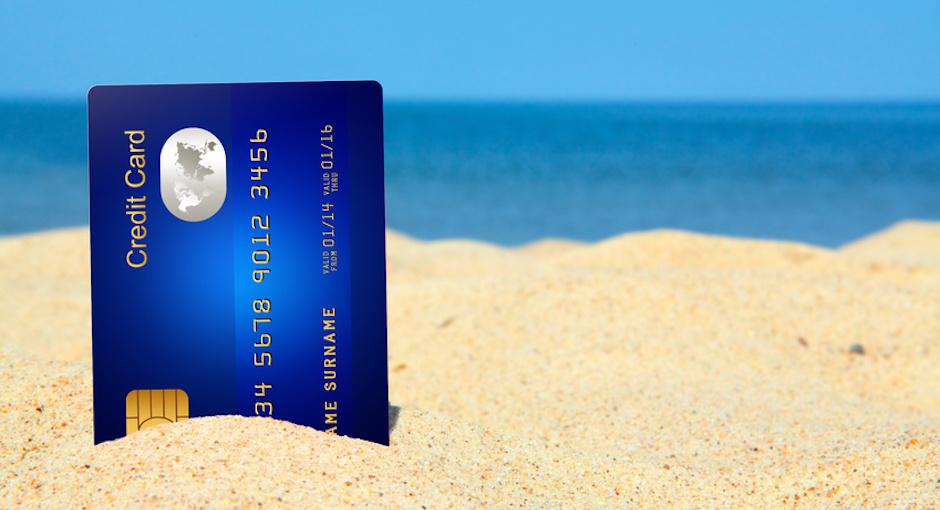 Kreditkarte am Strand für den Urlaub